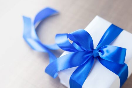 single white gift box with blue ribbon on wood table close up. gift for man