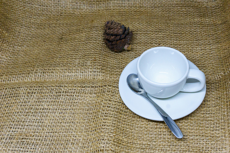 empty white coffee cup on the sackcloth and pine cones