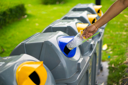Young girl hand dropping plastic bottle into recycle bin and there are waste separation bin for different kind of garbage to safe environment. pollution or waste management business concept Stock Photo