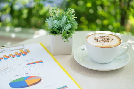 business analysis information document with latte art coffee and small plant on the table near the long modern windows glass during meeting in the cafe
