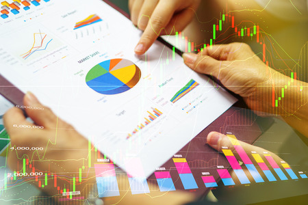 business women hand holding business analysis document while colleague point finger on pie chart with great teamwork collaborative cooperation during discussion in meeting mixed stock market graph Stock Photo