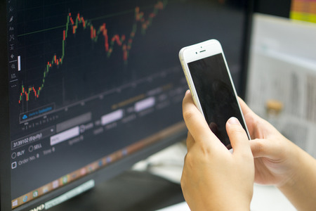 Business and finance concept. man use smart phone with mixed stock chart background