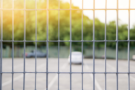 close up Metal grille or fence public of temporary Car Parking Stowage Barrier with blurred background. can be use as safety concept