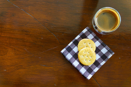 man drinking water: top view of espresso coffee with two pieces of cookies on piece of cloths on the wooden table with copy space for text.
