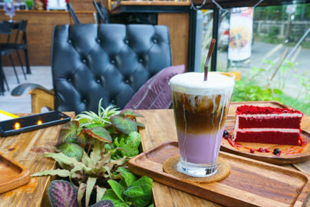 close up. iced sweet potato latte coffee in glass and red velvet cake on the wooden plate on the table with blurred cafe background