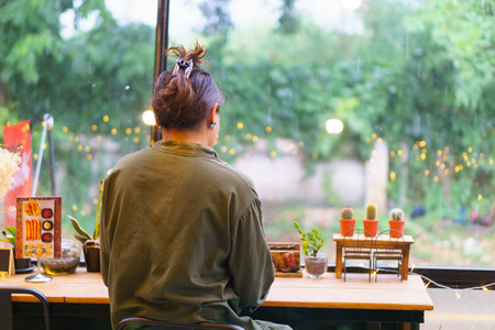 young beautiful asian female drinking espresso coffee at the old vintage bar table near long modern windows glass in cafe Stock Photo