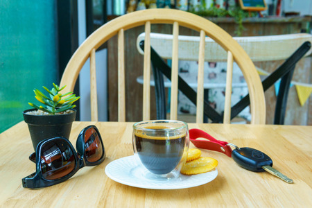 close up and front view. espresso coffee in transparent cup with two cookies and sunglasses and car key and mock up plant on the wooden table. travel, holiday concept. Stock Photo