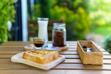 wind blown: iced cube coffee latte with milk and shot of espresso and Toast topping with condensed milk and cutlery on the wooden table in the garden with copy space for text Stock Photo