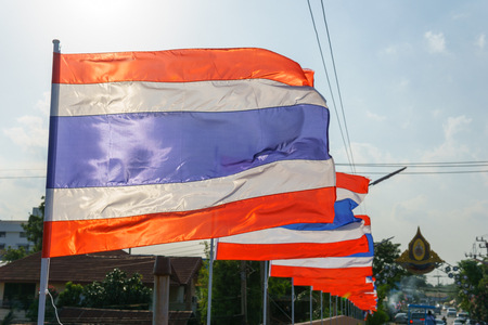 wind blown: close up. thai flags on the pole blown by wind at the bridge in sunny day Stock Photo