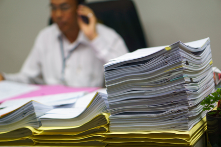 job deadline: Pile of organized but unfinished business documents on desk with businessman talking on  smartphone and sitting on the chair in the office background,  business and busy job concept Stock Photo