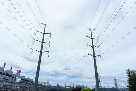 oil and gas industry: two high voltage electricity pylon and transmission line with power plant background and cloudy blue sky Stock Photo