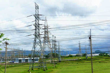 high tech: high voltage electricity pylon with transmission line near electricity station in the filed with cloudy sky.