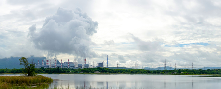 panorama view of coal fire power plant release steam to sky from stack tower. electricity, climate change and power plant concept.