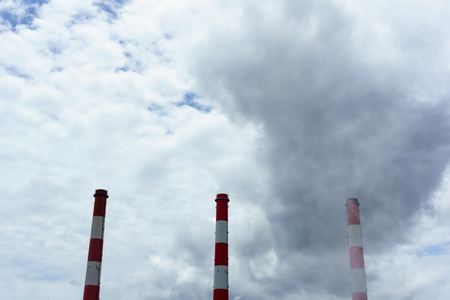 exhaust system: close up of power plant smoke chimneys with blue cloudy sky Stock Photo
