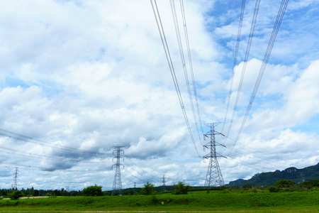 high voltage electricity pylon and transmission line in the field with blue sky and cloud Stock Photo