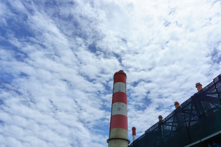 high tech: close up of coal fired power plant and smoke stack for release steam with cloudy blue sky. electricity concept.