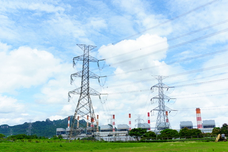 oil and gas industry: high voltage electricity pylon and transmission line on the filed with coal fired power plant and blue sky with cloud background Stock Photo