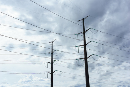 high tech: two high voltage electricity pylon with cloudy sky at dusk