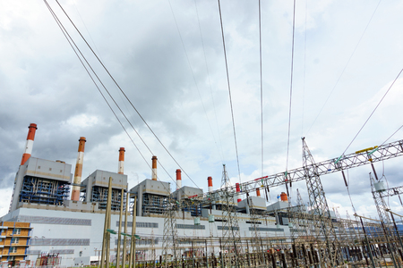 group of coal fired power plant and stack with high voltage electricity station and pylon. electricity concept.