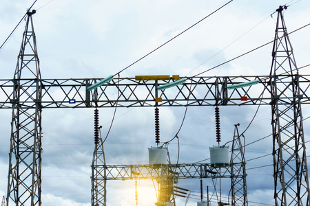 high tech: high voltage electricity pylon and circuit breaker with cloudy sky and sun ray