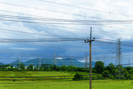 high tech: low voltage pole with high voltage electricity pylon and transmission line background in the filed with cloudy sky. Stock Photo
