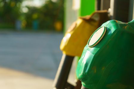 oil and gas industry: petrol pump nozzle for fill fuel at gas station in sunny day