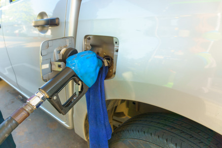 oil and gas industry: petrol pump nozzle filling oil gas fuel to the car