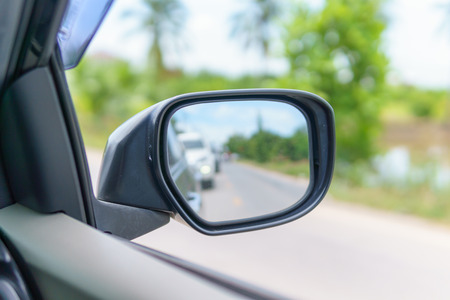 Rearview mirror with traffic jam on the asphalt rural road at countryside. travel or traffic of transportation concept Standard-Bild
