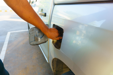 oil and gas industry: man hand opening the gas tank of the car Stock Photo