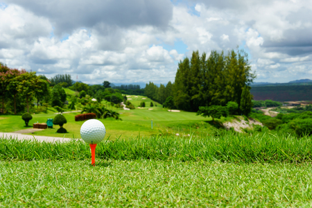 hole: close up of white golf ball on orange tee on green grass with blue sky and cloud and view of mountain background in sunny day. copy space for your text.