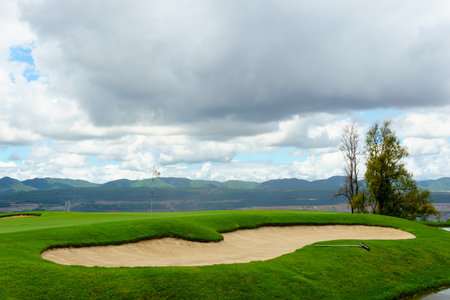 beautiful idyllic view green with sand trap and white flag and view of mountain, blue sky with clouds