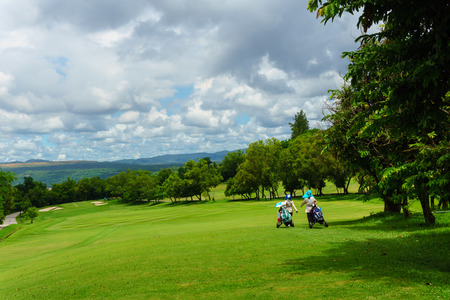 hole: golfer walking with caddies in golf course with view of mountain and blue sky and cloud in sunny day