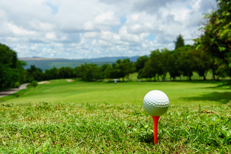 hole: close up of white golf ball on orange tee on green grass with blue sky and cloud. copy space for your text.
