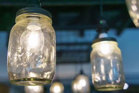 electricity light bulb glowing in the transparent vase hanging on the ceiling for abstract background or special occasion background.