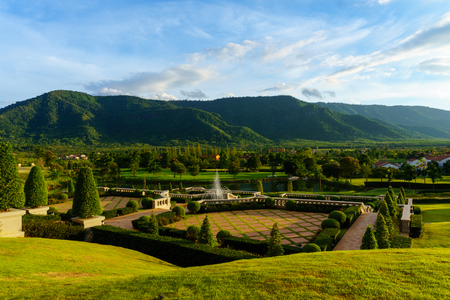 panorama view of public garden with blue sky and cloud and mountain background.