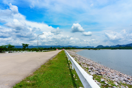 road along the dam with cloudy blue sky. journey or milestone abstract concept Stock Photo
