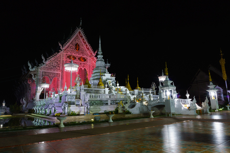 landscape view of ancient burmese style chiang rai temple turning color light on at night. lampang, thailand. Stock Photo