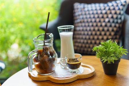 iced cube coffee latte with milk and shot of espresso and small mock up plant on the wooden table in the cafe with copy space for text. Stock Photo