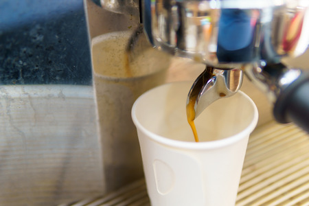 Close up of espresso coffee pouring from coffee maker machine to white paper glass shot. barista coffee brewing concept. Stock Photo