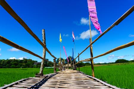 """close-up van Landelijke bamboe brug pad naar rijstvelden met blauwe lucht en pluizige wolk in zonnige dag op het platteland. lampang, noordelijk deel van Thailand. Bridge naam """"Sapan Boon Wat Pa That San Don"""""""