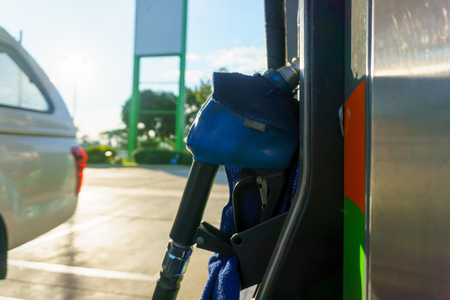 car waiting for fill fuel with petrol pump nozzle at gas station in sunny day before gas price is up tomorrow. Stock Photo