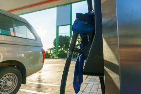 oil and gas industry: car waiting for fill fuel with petrol pump nozzle at gas station in sunny day before gas price is up tomorrow. Stock Photo