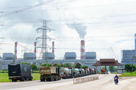 august 8, 2017. lampang, thailand. row of carriage truck with coal fired power plant release steam to sky and high voltage electricity pylon background.