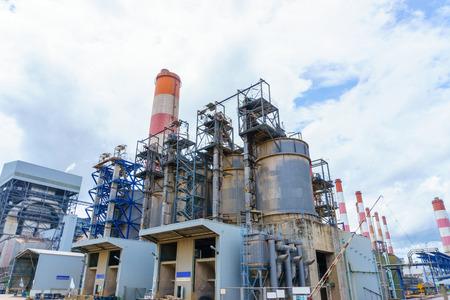 torre de la pila de humo de la central eléctrica con el cielo azul y nublado.