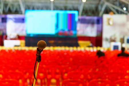 close up of microphone in the seminar hall for speaker or singer with blurred row of red plastic chair and big led monitor screen background. copy space for text. lecturer, speaker, seminar concept. Stock Photo