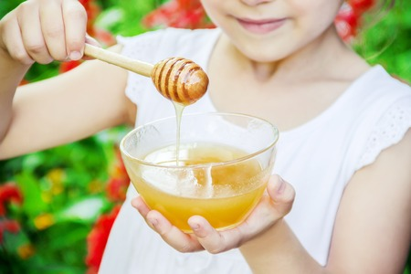 The child eats honey. Selective focus. nature food 스톡 콘텐츠