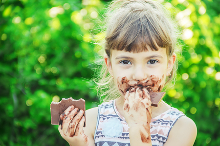A sweet-toothed child eats chocolate. Selective focus. nature. 版權商用圖片 - 104823164