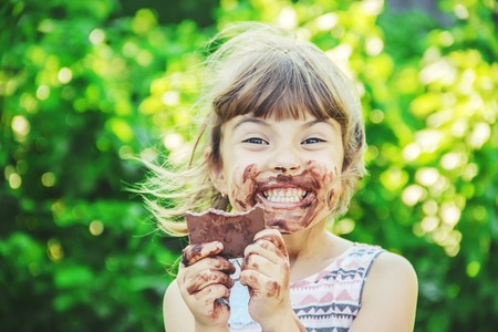 A sweet-toothed child eats chocolate. Selective focus. nature. 스톡 콘텐츠 - 104823168