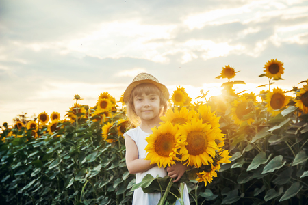 A child holding bright yellow sunflowers in the field in selective focus