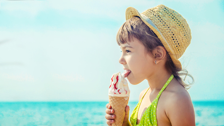 the child eats ice cream on the sea. Selective focus. summer. Stok Fotoğraf
